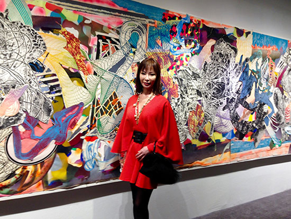 Yung Hee Kim with a collage by Frank Stella in the background at Dominique Levy